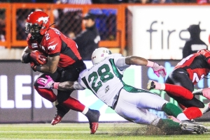 Calgary running back Joc Sanders breaks a tackle from Roughrider defensive back Mark LeGree. The Stampeders defeated the Roughriders to improve to 14-2 on the season.