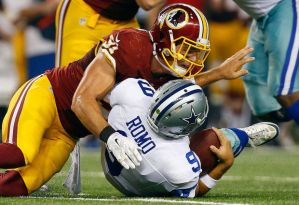 Dallas quarterback Tony Romo is sacked by the Washington Redskins defence. Romo suffered minor fractures in his back in a Cowboy overtime defeat.